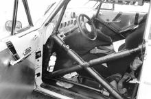 The race car interior mixes '55 components with aluminum wallpaper and a full NASCAR-style rollcage. Note that the controls for the Lincoln's power windows were retained.